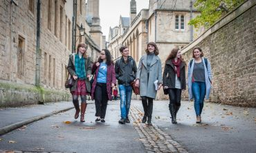 Six students walking to lecture along Brasenose Lane