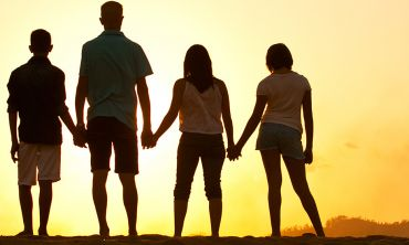 Family silhouetted by sunset