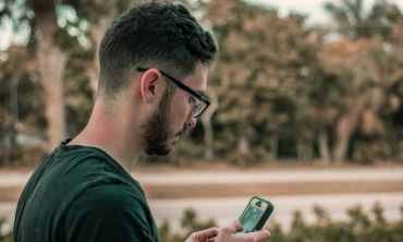 Man in glasses looking at his smartphone. Photo by Jacob Townsend on Unsplash