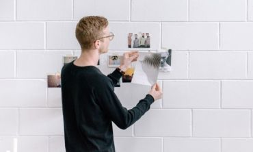 young man hanging posters on a white wall