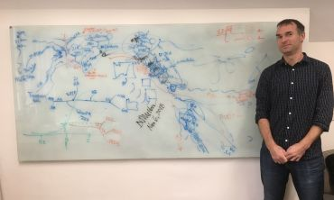 Professor Greger Larson tands next to a white board on which he, Angela Perri [Durham University] and David Meltzer [SMU] mapped archaeological sites and populations of dogs and people. The academics' two day effort resulted in new insights into the close
