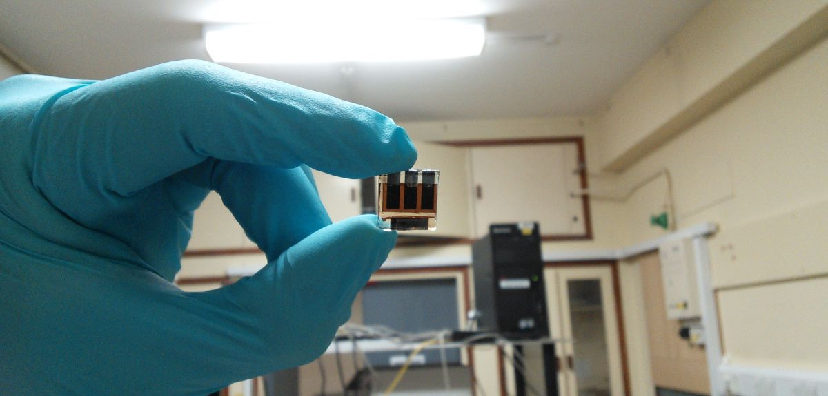 A gloved hand holds a perovskite cell up to the light.