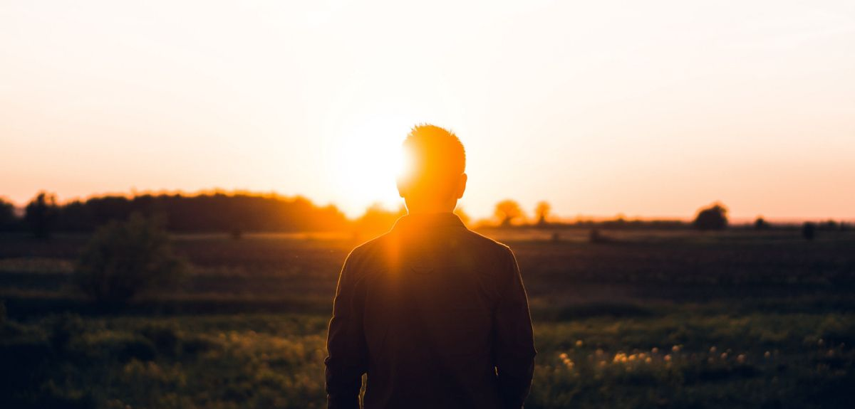 Person stood in front of a sunrise. Photo by Warren Wong on Unsplash