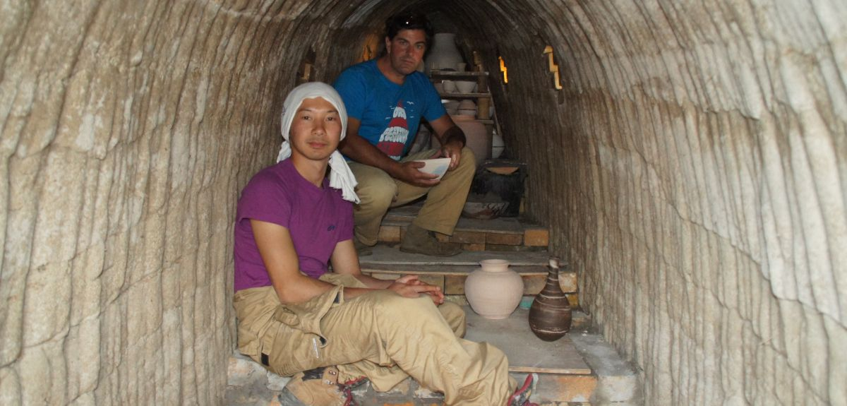 Ishida Kazuya,a potter from Bizen in Japan, crawls into the kiln to load the pots before firing. Dr Robin Wilson from Oxford University is behind him.