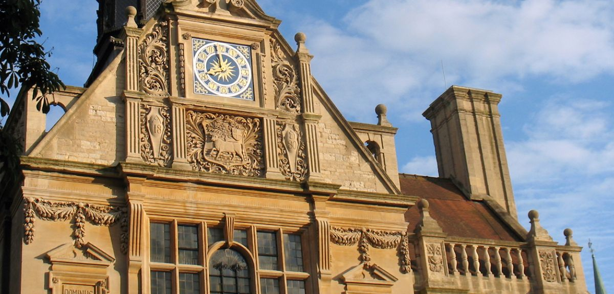 The History Faculty building with clock against a blue sky