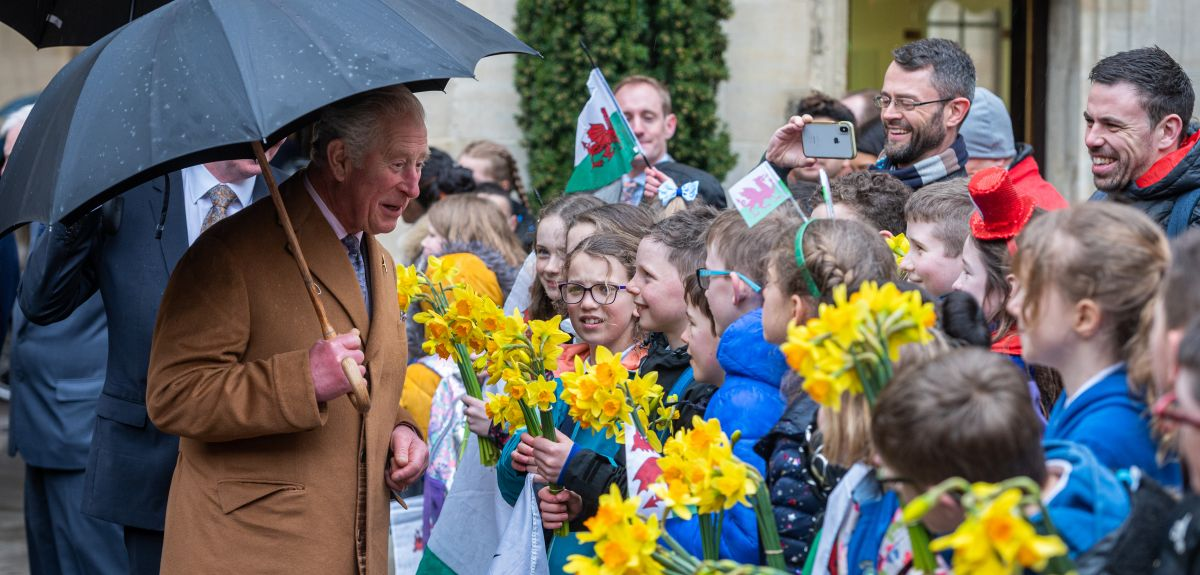HRH Prince Charles is greeted by 60 primary school children from three Welsh schools at Jesus College. Image by John Cairns