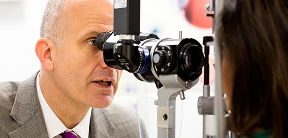 Professor Robert MacLaren examines a patient's eyes