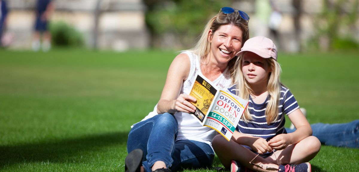 Woman and young girl sit on the grass reading Oxford Open Doors brochure