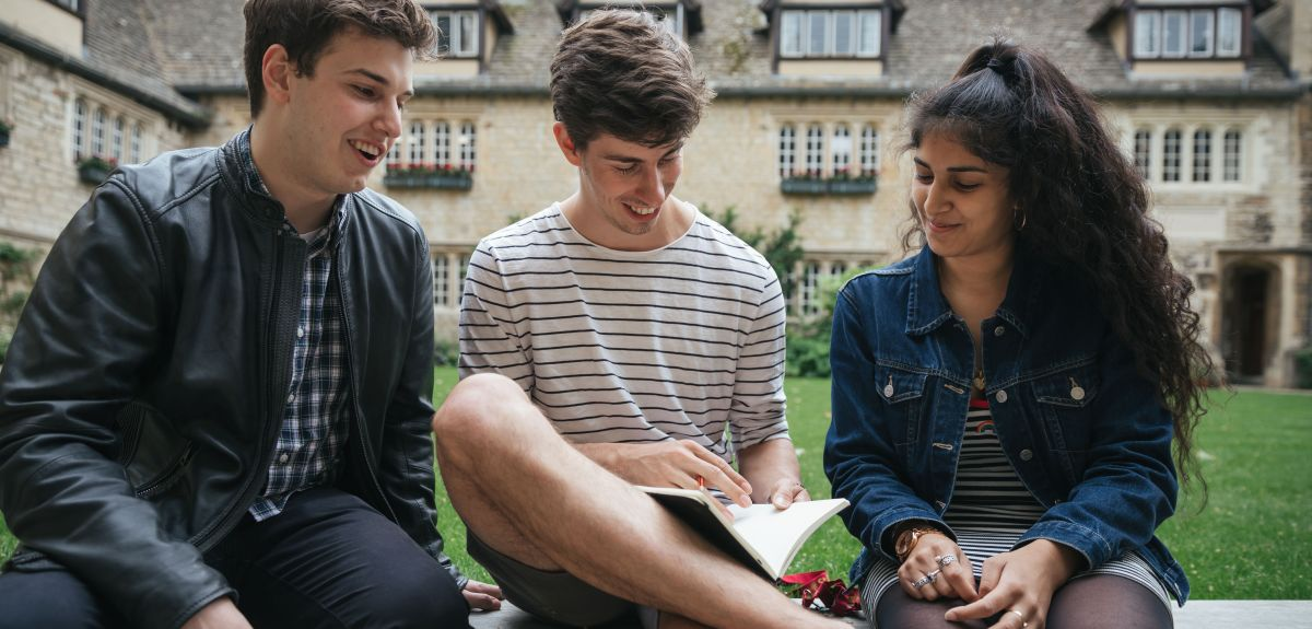 Three students sitting on a bench in a college garden.