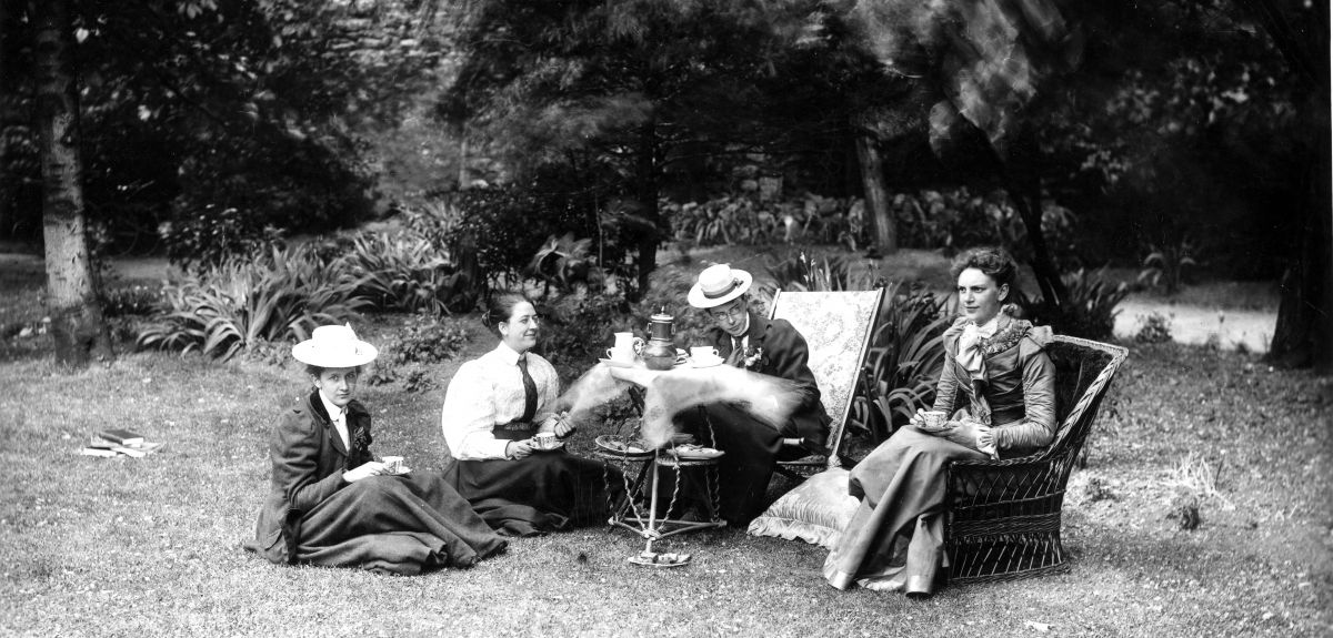 Four women have a picnic on a lawn at Somerville College