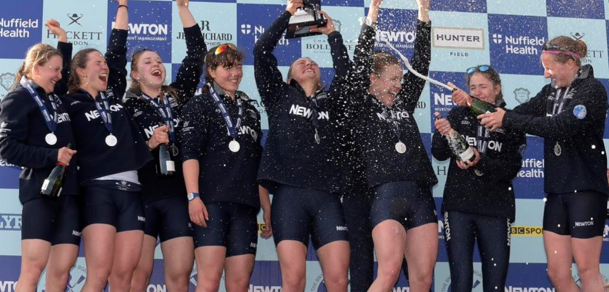 The victorious women's crew hold up the trophy