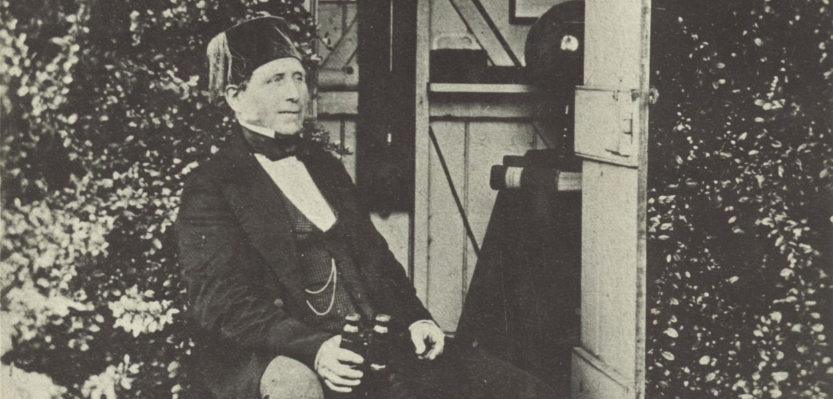 Black-and-white photograph of Francis Abbott, posing with bottles of beer and a fez
