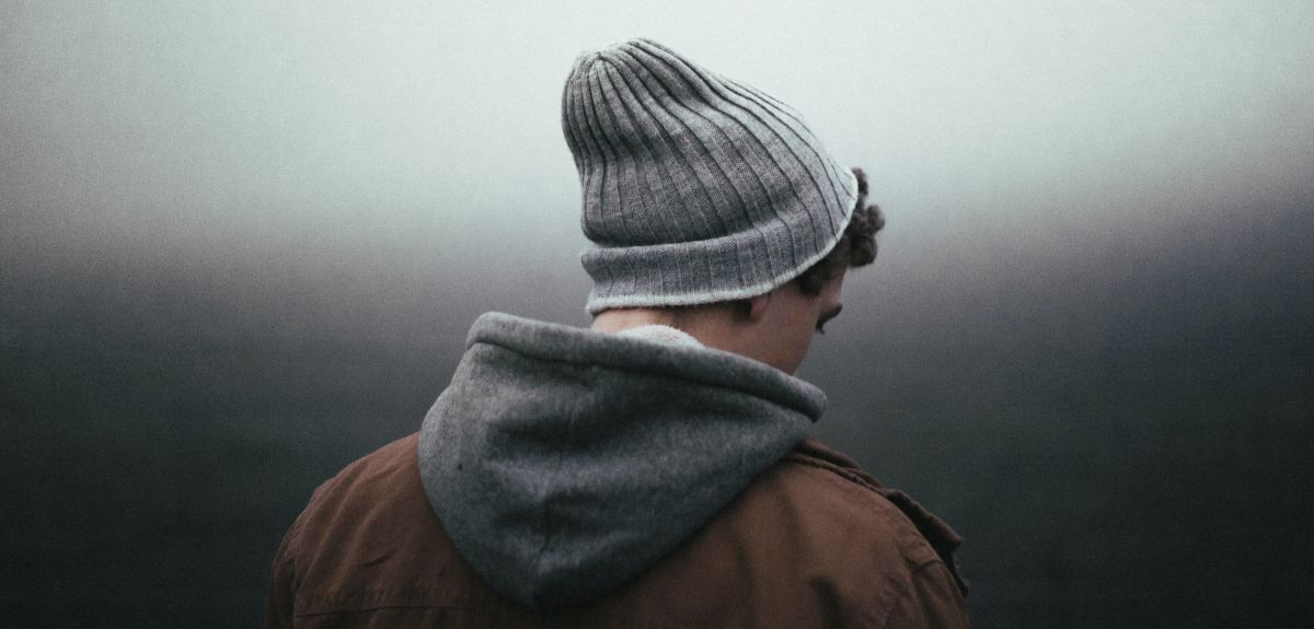 Man in hat and hoody outside in dark light. Photo by Andrew Neel on Unsplash