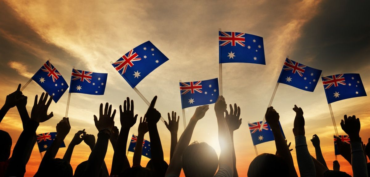Crowd of people holding mini Australia flags