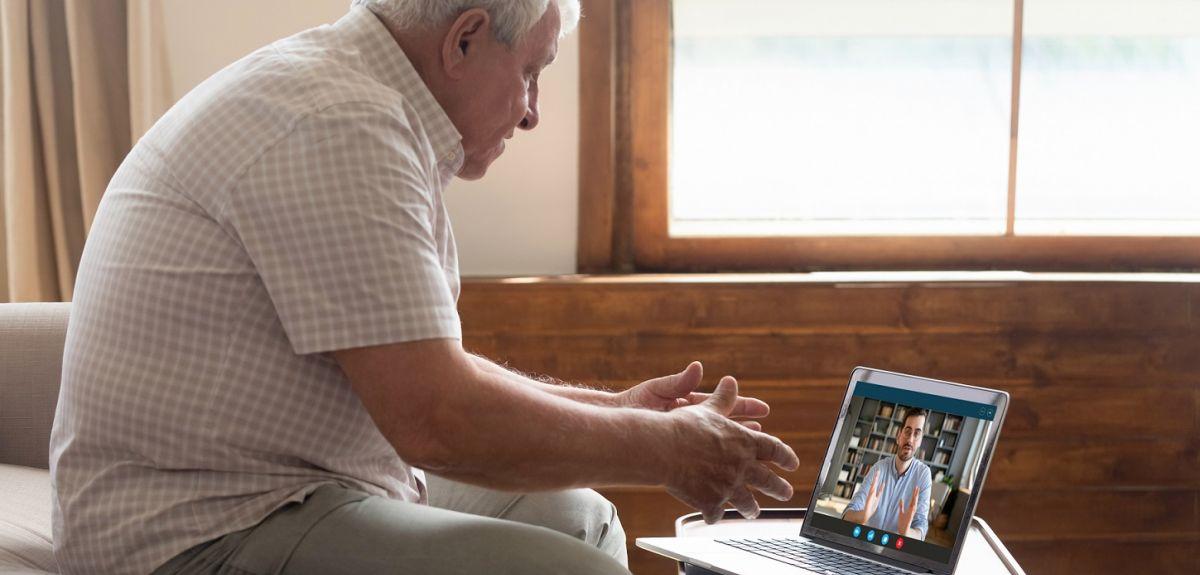 Mature older man sitting on sofa, looking at computer screen, having video call