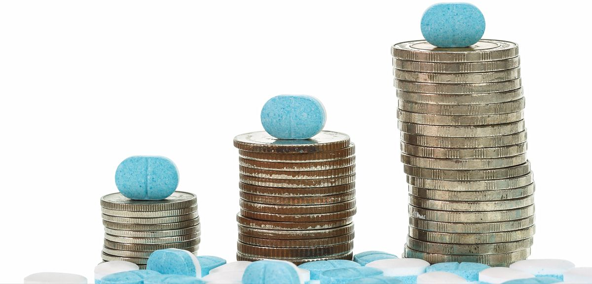 Close up pile of medicine and coin stack isolated on white background