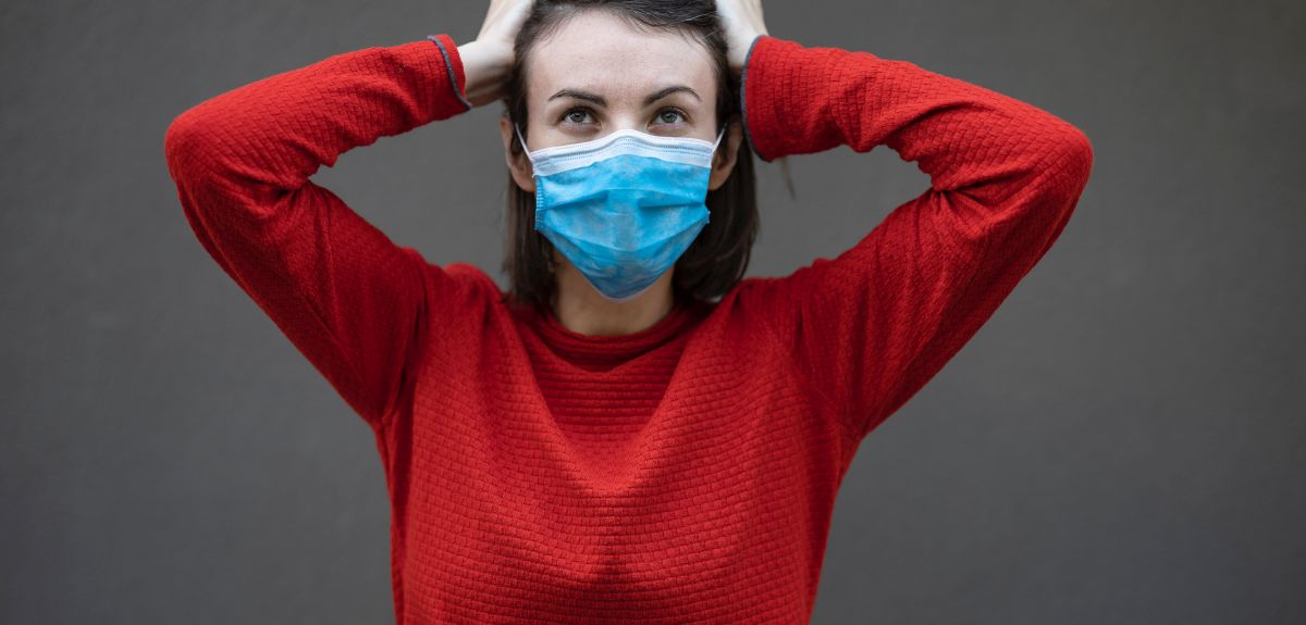 Woman in red sweater and mask. Photo by engin akyurt on Unsplash