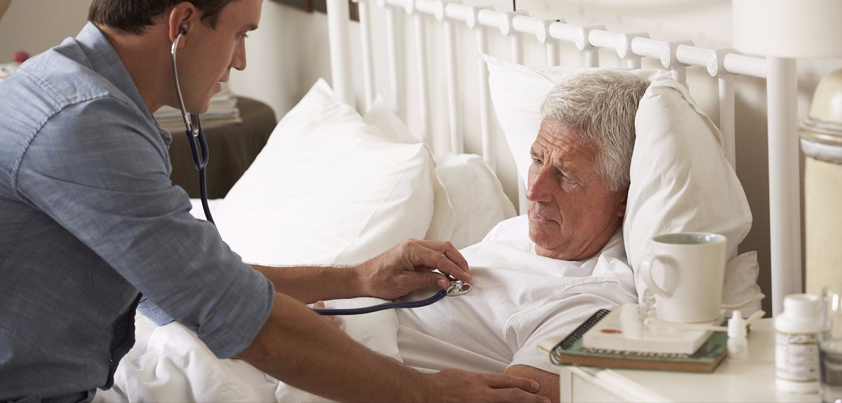 GP examines a patient on a home visit