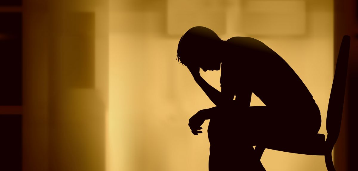 Silhouette of a man holding his head in his hand.