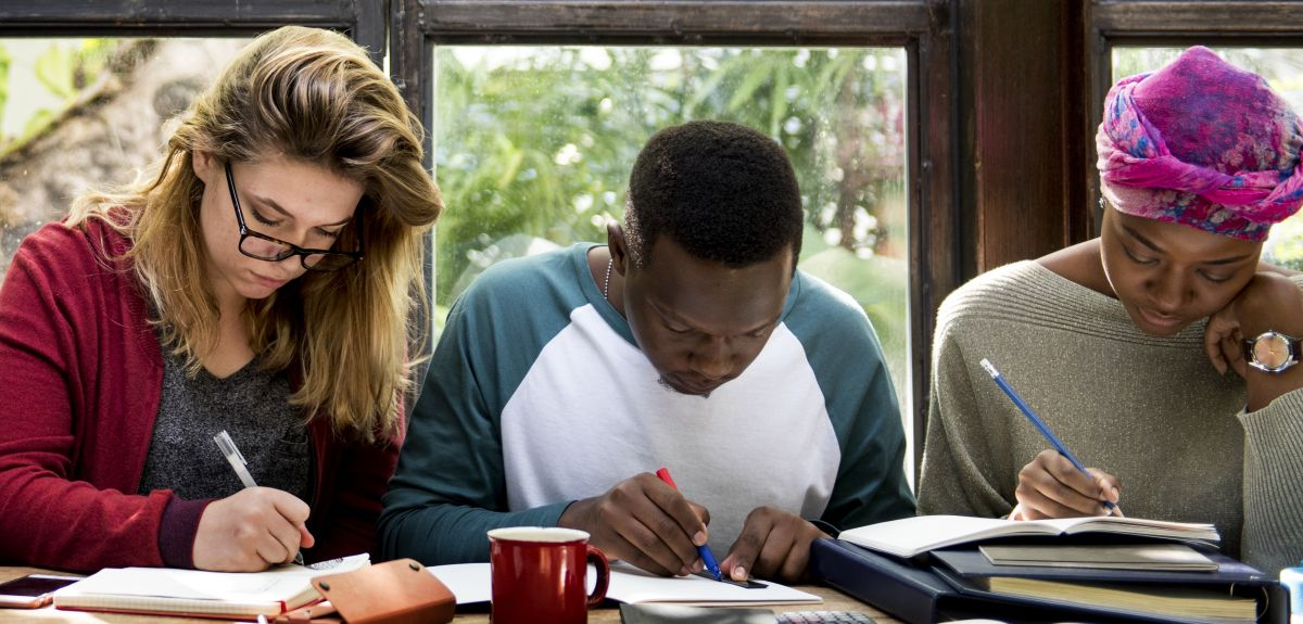 Three students revising and taking notes