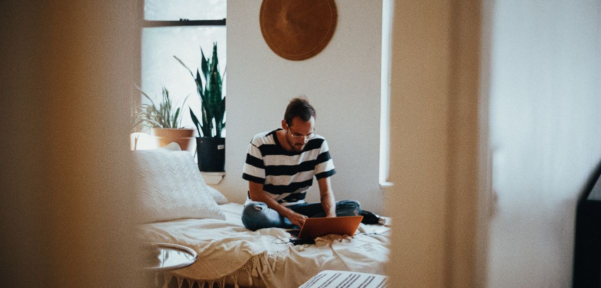 Man sat on bed on laptop. Photo by Parker Gibbons on Unsplash