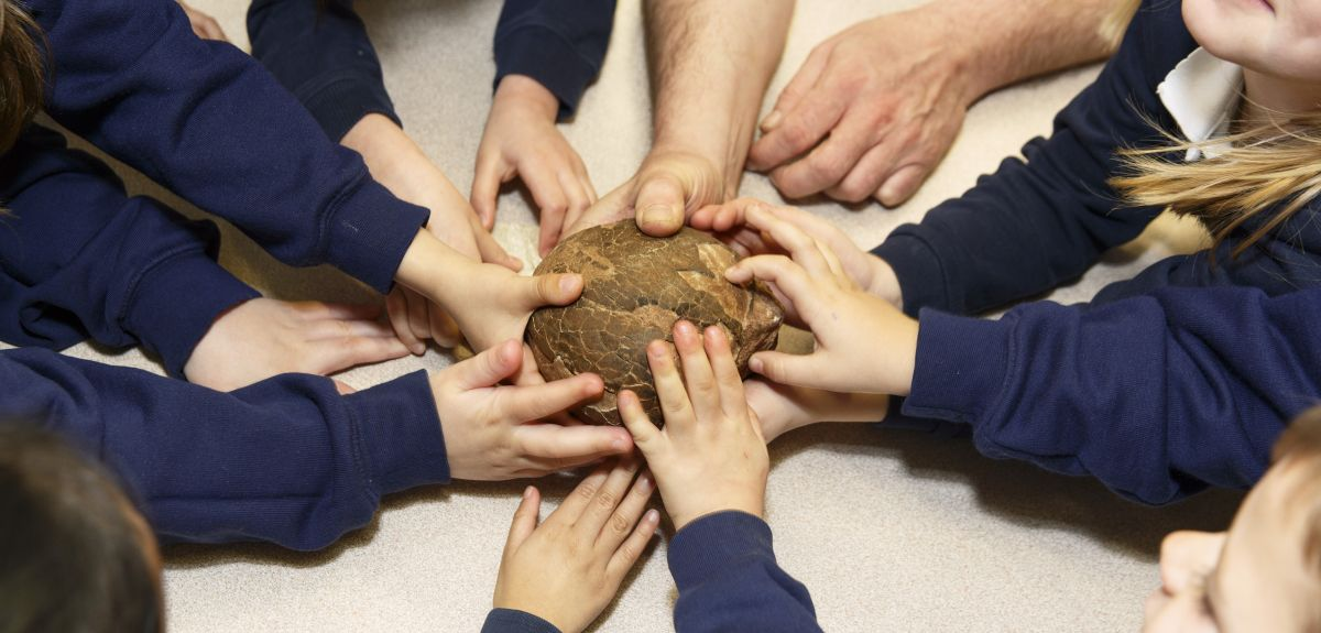 Children handlling a dinosaur egg in the Museum, by Martin Parr