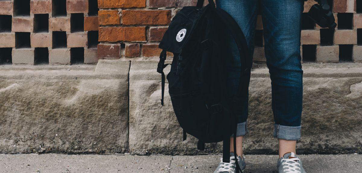 Student standing with a rucksack. Image credit: Scott Webb on Unsplash