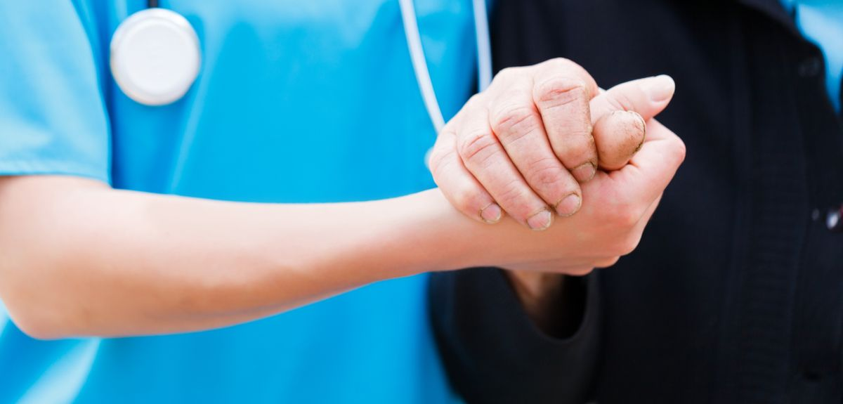 Nurse holding an elderly person's hand