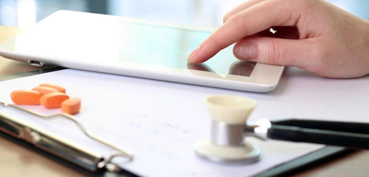 Doctor on tablet with pills and stethoscope