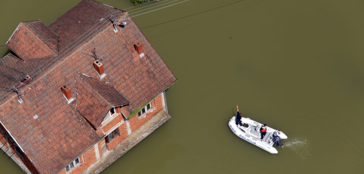 Boat travels to the aid of flooded house.