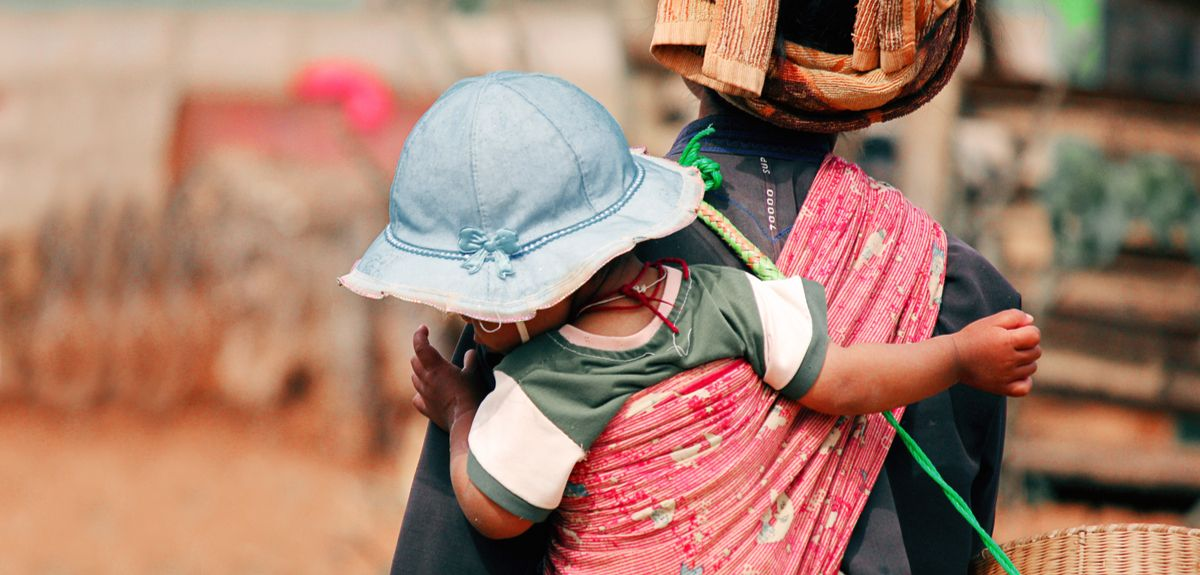 Young mother in Africa carries baby on her back