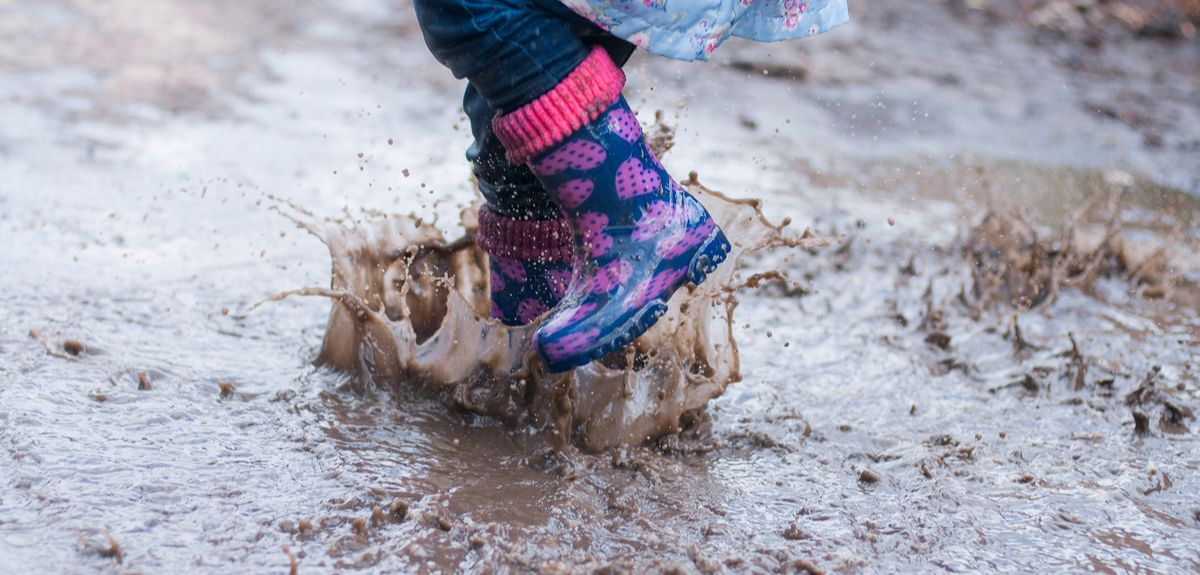 Child jumping in a puddle