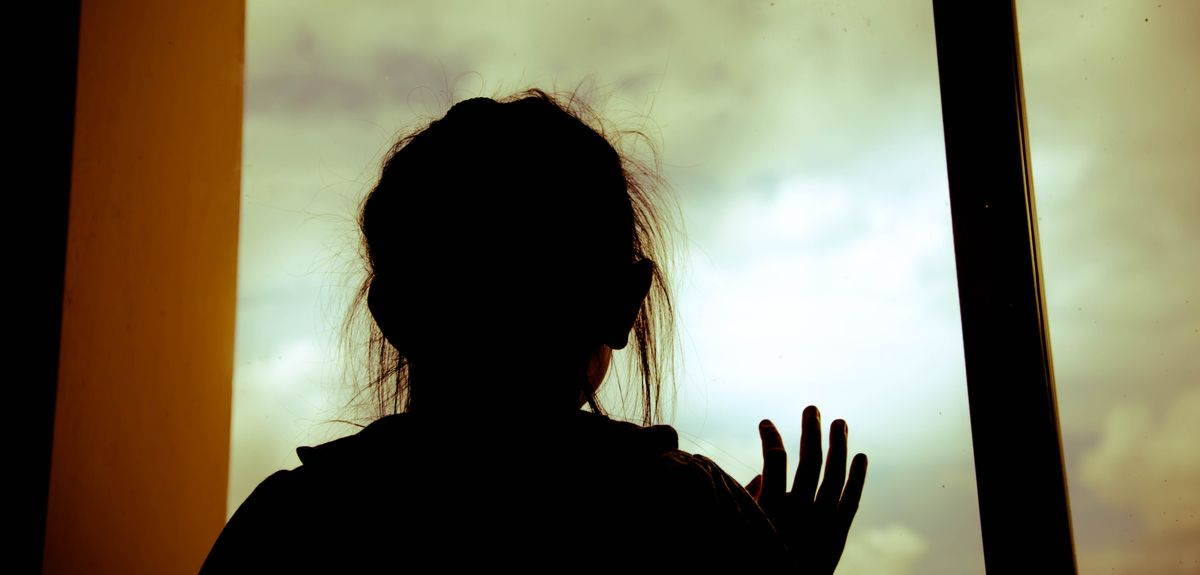 Silhouette of a child standing at a window
