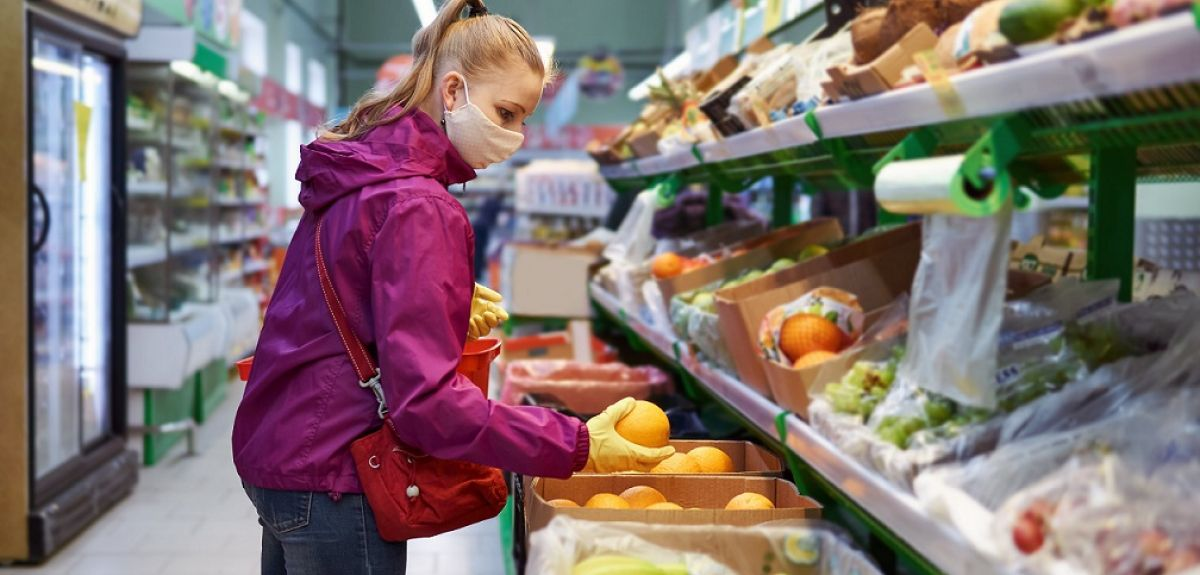 Woman in a supermarket looking at fruit wearing face mask