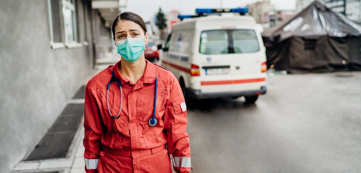 Distressed paramedic in front of isolation hospital facility