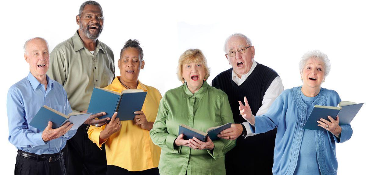 Six senior adults happily singing from song books