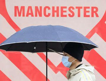 Man with umbrella beneath Manchester sign