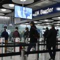 Travellers queue at passport controls at UK airport.