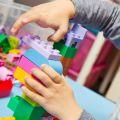 Child plays with building bricks at nursery school