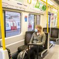 Women sits on London Underground train wearing a face mask