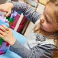 Child plays with building bricks at nursery school