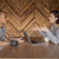 Two people sitting at a table talking. Credits: Ekatarina Bolovtsovia via Unsplash