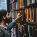 Man selecting a book from a library bookshelf. Photo by Devon Divine on Unsplash