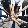 A team of people putting their hands together in a circle